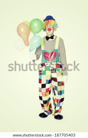 full length portrait of a clown with balloons - stock photo