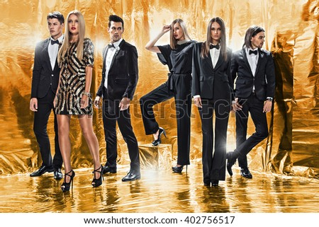 Full length portrait of a confident business team standing on a gold background - stock photo