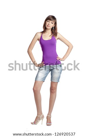 Full length portrait of a confident young female standing on white background - stock photo