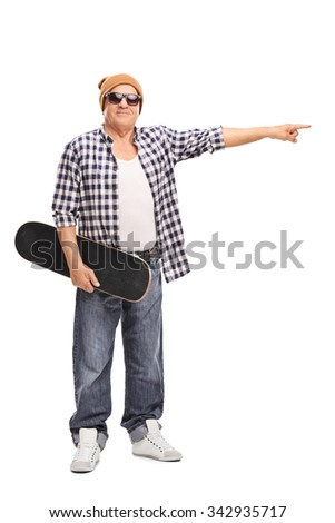 Full length portrait of a cool senior holding a skateboard and pointing towards the right with his hand isolated on white background - stock photo