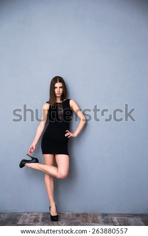 Full length portrait of a cute fashion woman in sexy black dress. Touching her heels. Leaning on the gray wall. Looking at the camera - stock photo