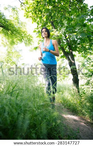 Full length portrait of a cute fitness woman running outdoors in park. Looking away - stock photo