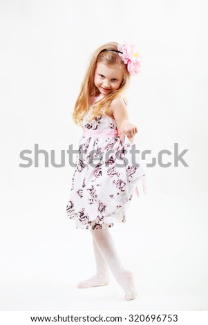 Full length portrait of a cute little blonde girl dancing against white background - stock photo