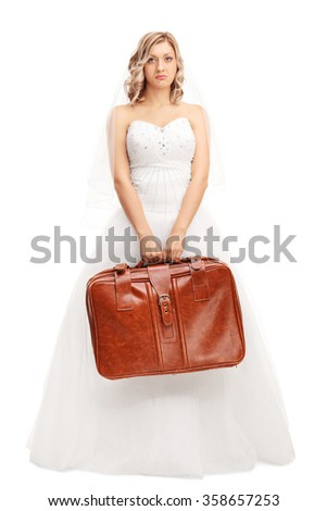 Full length portrait of a disappointed bride holding a brown suitcase and looking at the camera isolated on white background - stock photo