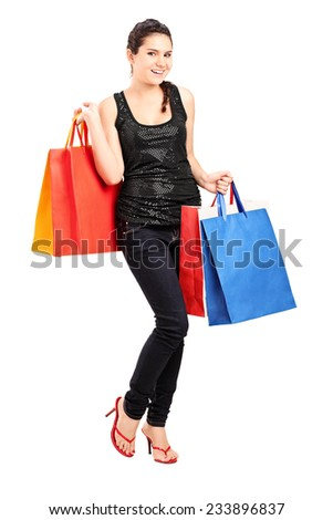 Full length portrait of a fashionable female holding bunch of shopping bags isolated on white background - stock photo