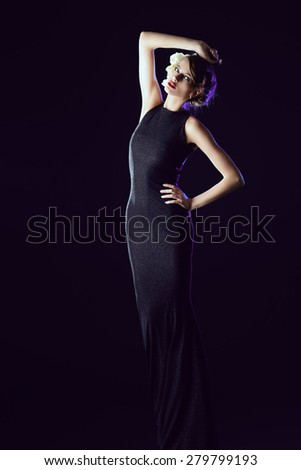 Full length portrait of a fashionable model posing in long black dress over black background. Beauty, fashion.  - stock photo