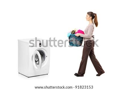 Full length portrait of a female holding a laundry basket going towards a washing machine isolated on white background - stock photo