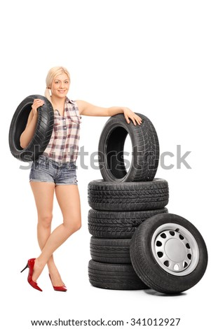 Full length portrait of a female mechanic holding a car tire and standing next to a stack of tires isolated on white background - stock photo