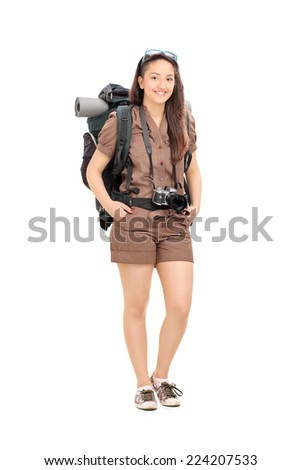 Full length portrait of a female traveler with hiking equipment posing isolated on white background - stock photo