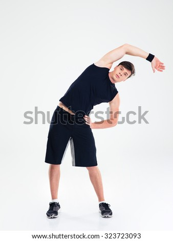 Full length portrait of a fitness man doing stretching exercises isolated on a white background - stock photo