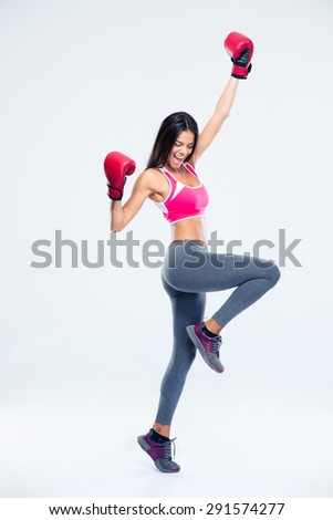 Full length portrait of a fitness woman in boxing gloves celebrating her success over gray background - stock photo