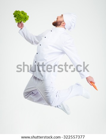 Full length portrait of a funny chef cook dancing with vegetables isolated on a white background - stock photo