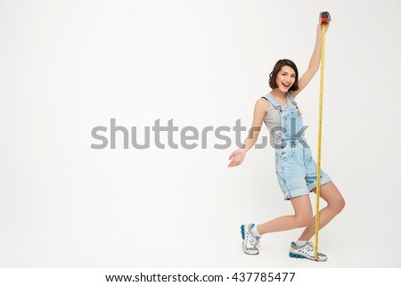 Full length portrait of a funny pretty girl, in gray shirt and denim overall, holding measure tape, isolated on white background - stock photo