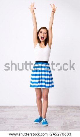 Full length portrait of a funny woman with raised hands up - stock photo