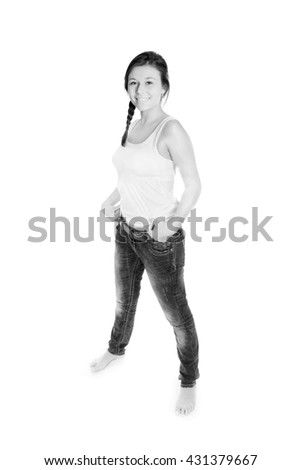 Full length portrait of a girl wearing jeans and a white top, isolated on white studio background, black and white photo - stock photo