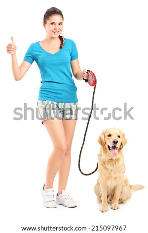 Full length portrait of a girl with a dog giving a thumb up isolated on white background - stock photo