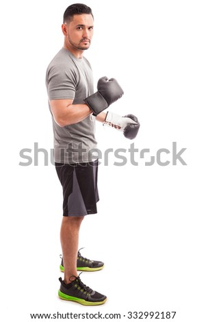 Full length portrait of a good looking young man wearing boxing gloves on a white background - stock photo