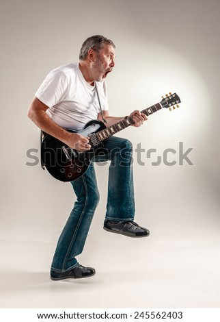 Full length portrait of a guitar player - stock photo