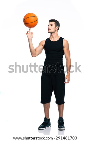 Full length portrait of a handsome basketball player spinning ball on his finger isolated on a white background - stock photo