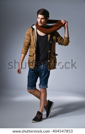 Full length portrait of a handsome man wearing jeans clothes and a coat. Men's beauty, seasonal fashion. Studio shot - stock photo