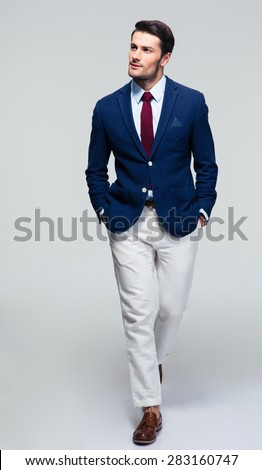 Full length portrait of a handsome pensive businessman walking over gray background - stock photo