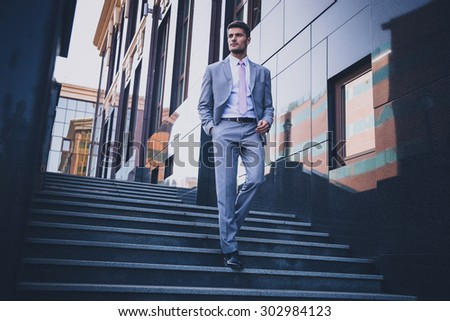 Full length portrait of a handsome thoughtful businessman walking on the stairs outdoors  - stock photo