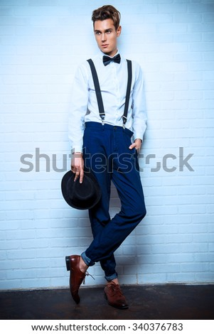 Full length portrait of a handsome young man in elegant suit posing by a white brick wall. Business. - stock photo