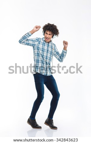 Full length portrait of a happy afro american man listening  music in headphones and dancing isolated on a white background - stock photo
