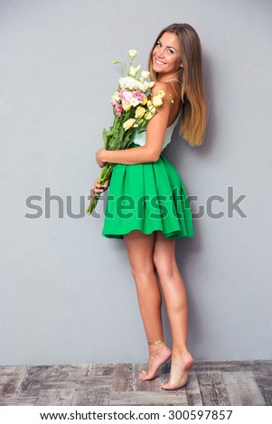 Full length portrait of a happy attractive woman posing with flowers on gray background. Looking at camera - stock photo