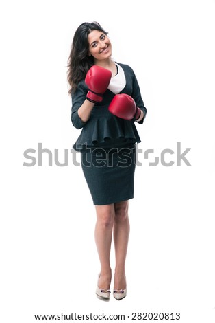 Full length portrait of a happy businesswoman standing in boxing gloves and looking at camera - stock photo