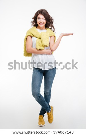 Full length portrait of a happy casual woman holding copyspace on the palm isolated on a white background - stock photo