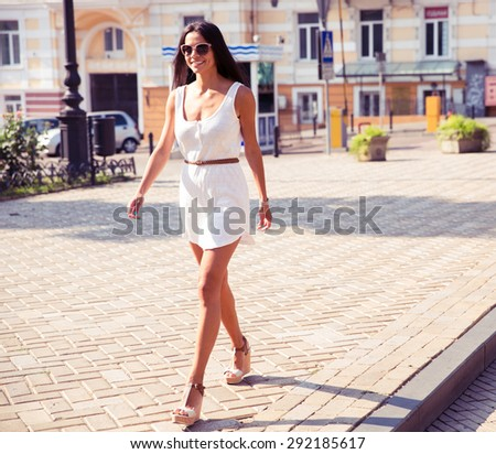 Full length portrait of a happy fashion woman walking in town - stock photo