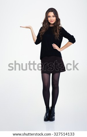 Full length portrait of a happy girl holding copyspace on the palm isolated on a white background - stock photo