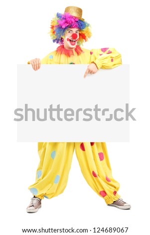 Full length portrait of a happy male clown pointing on a blank panel isolated on white background - stock photo