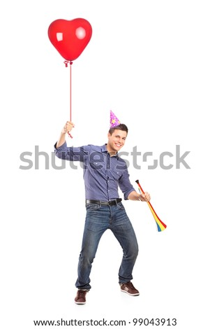 Full length portrait of a happy male holding a balloon and a horn isolated on white background - stock photo