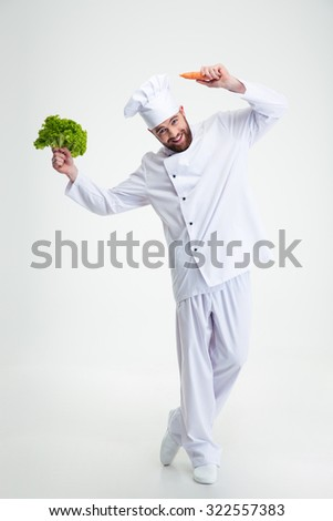 Full length portrait of a happy man dancing with vegetables isolated on a white background - stock photo