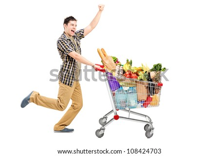 Full length portrait of a happy man pushing a shopping cart, isolated on white background - stock photo