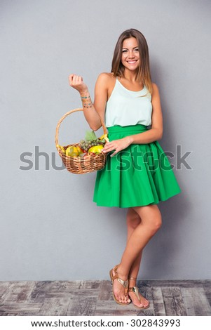Full length portrait of a happy pretty girl holding basket with fruits over gray background - stock photo