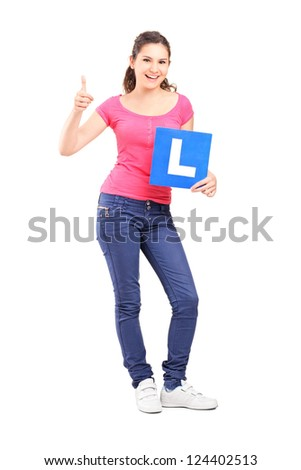 Full length portrait of a happy teenager holding L plate and giving a thumb up isolated against white background - stock photo