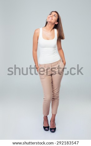Full length portrait of a happy woman looking up over gray background - stock photo