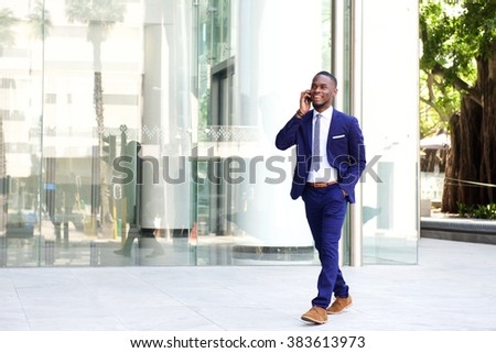 Full length portrait of a happy young businessman walking in the city and talking on mobile phone  - stock photo