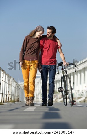 Full length portrait of a happy young couple walking outdoors with bike - stock photo