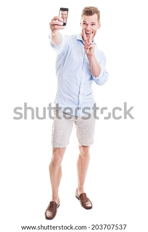 Full length portrait of a happy young man showing a peace sign and taking a SELFIE - isolated on white - stock photo