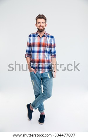 Full length portrait of a happy young man standing with laptop isolated on a white background and looking at camera - stock photo