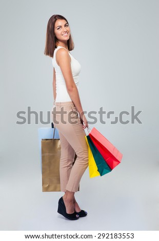 Full length portrait of a happy young woman holding shopping bags over gray background. Looking at camera - stock photo