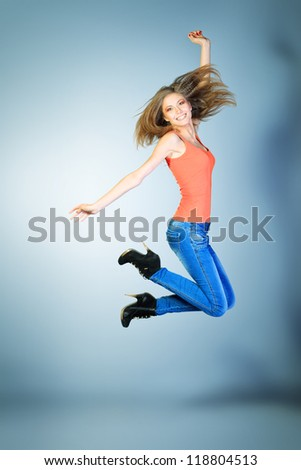 Full length portrait of a happy young woman jumping at studio. - stock photo