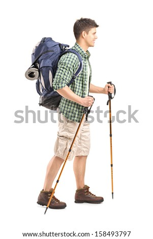 Full length portrait of a hiker with backpack and hiking poles walking isolated on white background - stock photo