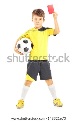 Full length portrait of a kid in sportswear holding soccer ball and giving red card isolated on white background - stock photo