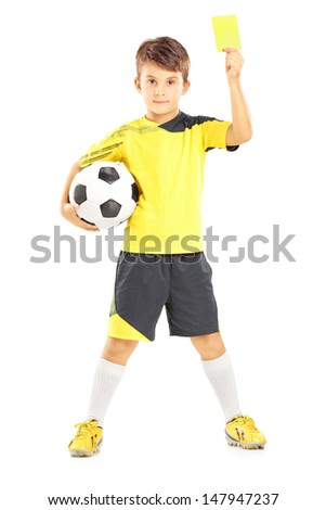 Full length portrait of a kid in sportswear holding soccer ball and giving yellow card isolated on white background - stock photo