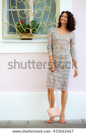 Full length portrait of a laughing beautiful middle-aged woman outdoors. fashion - stock photo